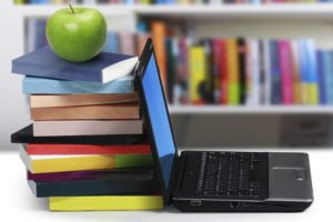 An apple on top of stacked books next to a laptop computer